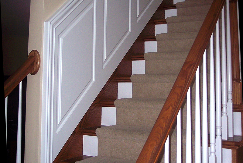 The wainscoting staircase panel ends just prior to the corner of the wall and the 3 1/4